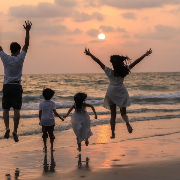 Asian young happy family enjoy vacation on beach in evening. Dad, mom and kid relax running together near sea while silhouette sunset. Lifestyle travel holiday vacation summer concept.