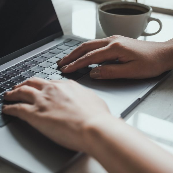 Closeup image of a woman working and typing on laptop keyboard with coffee cup on the table