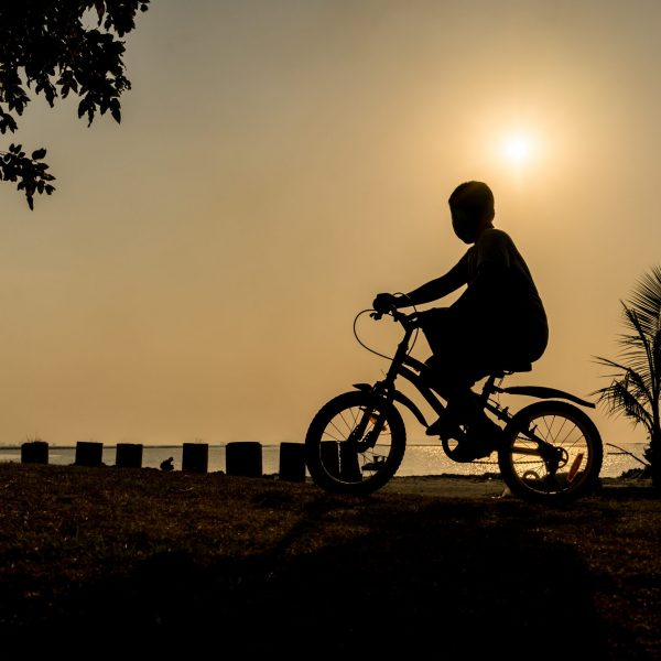 silhouette of the boy riding bike under the sunset near the beach on his holiday vacation relaxing time